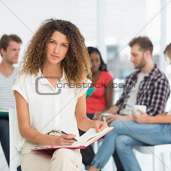 Focused woman writing while colleagues are talking behind her