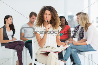 Focused woman looking at camera while colleagues are talking behind her