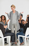 Rehab group applauding smiling woman standing up
