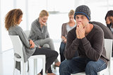 Upset man at rehab group with hands to face