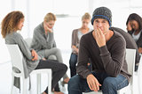 Upset man in rehab group looking at camera