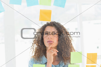 Thoughtful pretty designer looking at sticky notes on window