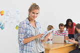 Smiling young designer using her tablet pc in front of her colleagues