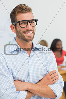 Attractive designer smiling at camera with colleagues behind him
