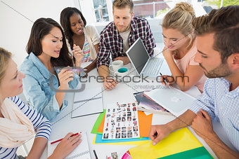Young design team going over contact sheets at a meeting