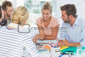 Smiling design team going over contact sheets at a meeting