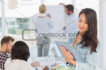 Asian woman using her tablet pc while her colleagues are working