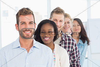 Design team standing in a line smiling at camera