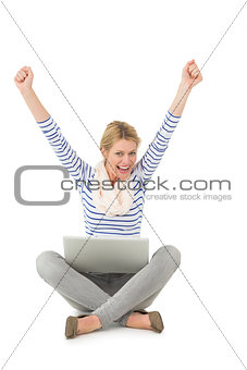 Pretty blonde cheering at camera with laptop sitting on floor