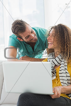 Smiling woman on the couch showing her colleague her laptop