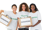 Happy team of volunteers smiling at camera holding donations boxes