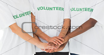 Team of volunteers putting hands together