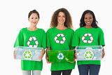 Team of environmental activists holding boxes smiling at camera