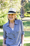 Happy woman wearing sunhat in park