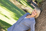 Woman leaning on tree trunk in parkland