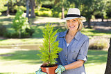 Woman holding potted plant in garden