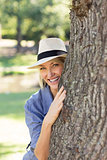 Smiling woman hiding behind tree trunk