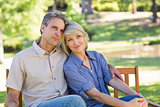 Loving couple relaxing on park bench