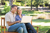 Couple using laptop on park bench