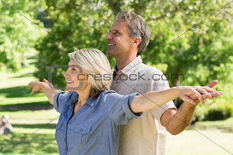 Couple arms outstretched in park