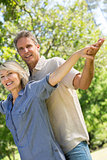 Couple with arms outstretched in park
