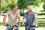 Couple riding bicycles in park