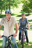Couple riding cycles in park