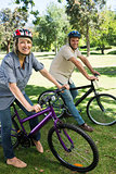 Couple riding bicycles in parkland