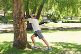 Man doing stretching exercise against tree