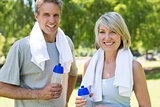 Couple holding water bottles in the park