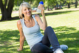 Relaxed woman holding water bottle in park