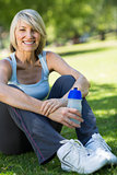 Woman holding water bottle in park