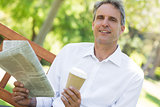 Businessman holding newspaper and coffee cup in park