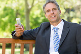Businessman with cellphone at park