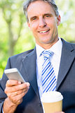 Businessman with mobile phone and disposable cup