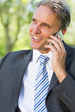 Happy businessman answering smartphone