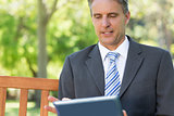 Mature businessman using digital tablet