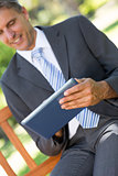 Businessman using digital tablet in park