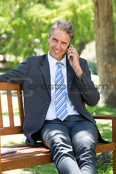 Businessman answering smart phone on park bench