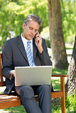 Businessman answering cellphone while using laptop