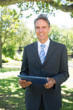 Happy businessman holding digital tablet