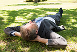 Businessman lying on grass in park