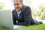 Businessman with laptop lying in park