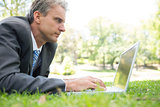 Businessman surfing on laptop in park