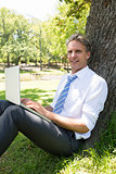 Confident businessman with laptop in park