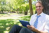 Businessman with digital tablet in park