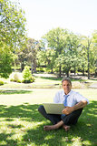 Businessman with laptop sitting in park