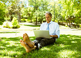 Businessman using laptop while relaxing in park