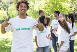 Portrait of volunteer pointing at tshirt