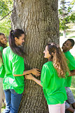 Environmentalists standing around tree trunk